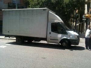 Foto on es veu un camió aparcat just al pas de vianants i el seu conductor al costat, mirant tranquilament com li faig la foto i com ens hem de desviar per a que poguem creuar el carrer amb un cotxet de nen