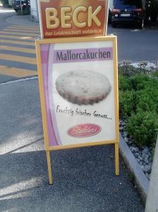 Cartell al carrer on s'anuncia una mena de reposteria amb la llegenda Mallorcakuchen