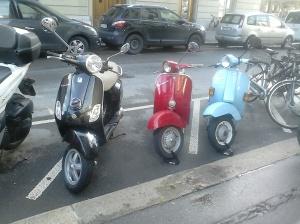 Tres motos Vespa, aparcades en bateria a un carrer de Bern. Negra, vermella i blau cel, respectivament.