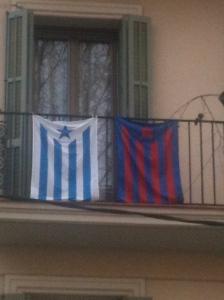 Banderes estelades del Barça i de l'Espanyol, penjades juntes a un mateix balcó
