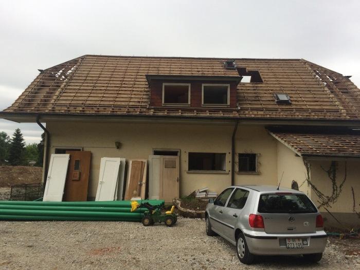 Casa amb el teulat de fusta desmuntat i les portes de fusta amuntegades al costat