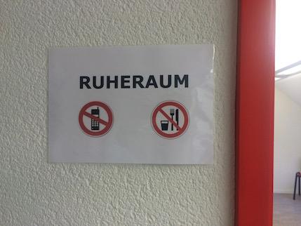 Cartell on es llegeix Ruheraum a sobre de les icones de prohibit fer servir el mòbil i prohibit menjar.