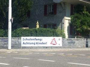 Pancarta penjada al carrer que mostra el rètol: 'Schulanfang: Achtung Kinder' (Comença l'escola: Atenció amb els nens)