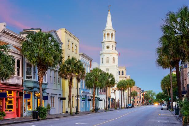 Carrer de Charleston, SC, amb cases baixes pintades de colors pastel, palmeres i una torre blanca.