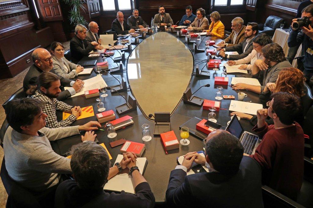 Els portaveus al Parlament de Catalunya reunits per escollir els senadors del Parlament al voltant d'una taula ovalada.