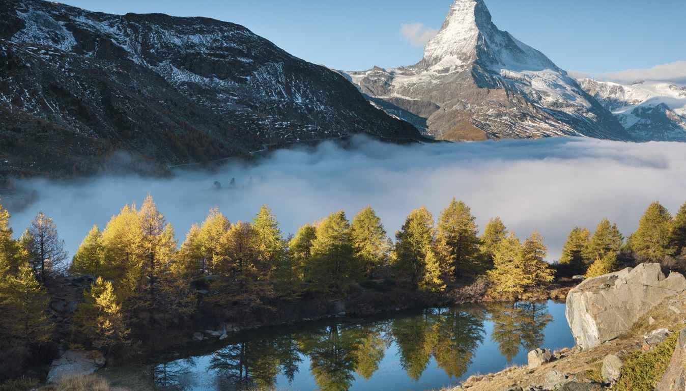 Vista panoràmica d'una vall amb el Montblanc al fons. En primer pla, un petit estany i una renglera d'arbres. Al darrera, un núvol de boira cobreix la vall. I més enllà, les muntanyes.