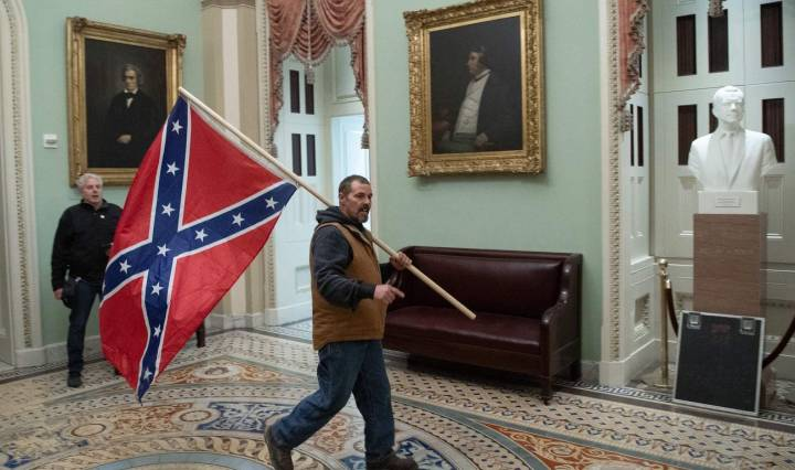 A protester carries the Confederate Flag inside Capitoll Hill building.