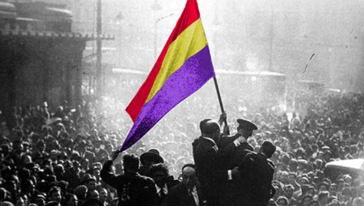 Foto en blanc i negre amb una munió de gent cel·lebrant l'adveniment de la Segona República. Un grup enlairat sobre alguna cosa sosté una bandera republicana, colorejada a la fotografia.