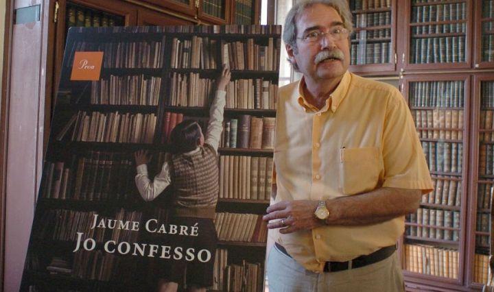 Jaume Cabré amb un cartell de la seva novel·la Jo confesso.